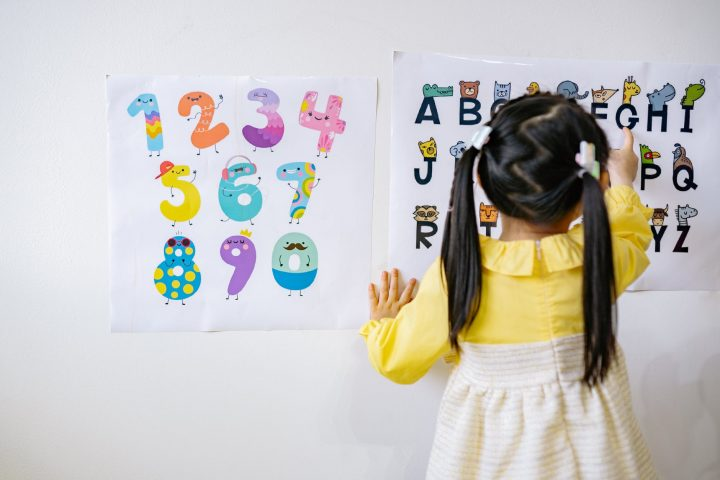 girl in yellow long sleeve dress reading the alphabets on wall